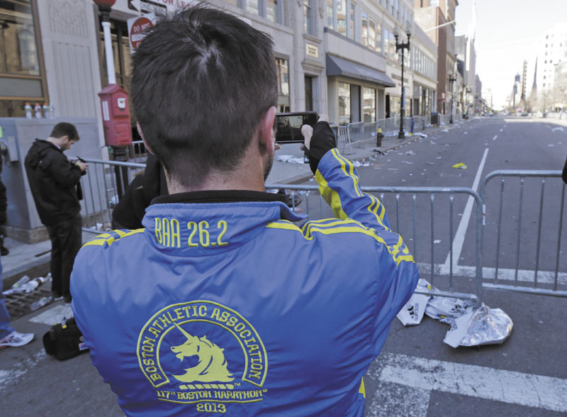 Paul McRae, a native of New Zealand now living in Jacksonville, takes a photograph of an empty Boylston Avenue near the Boston Marathon finish line, in Boston, Tuesday, April 16, 2013. Three people and more than 140 were injured when bombs exploded seconds apart close to the finish line on Monday. McRae finished the race before the explosions. (AP Photo/Charles Krupa)