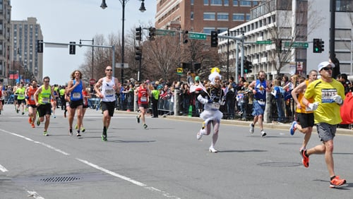 "Runners approach the ""1 Mile To Go"" marker Monday afternoon at the Boston Marathon. Just before 3 p.m. Monday, two bombs exploded 12 seconds apart at the marathon finish line, killing three and injuring 176 others."