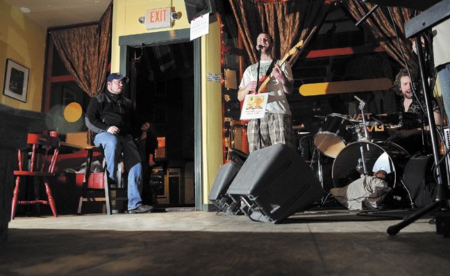 Sam Shain, center, plays the guitar while his brother, Josh, plays the drums with their band, The Scolded Dogs, at Higher Grounds in Hallowell Friday to an empty dance floor. The Office of the State Fire Marshal recently cracked down on establishments that permit dancing that don't meet code. The Scolded Dogs normally play to a packed house with several people dancing.