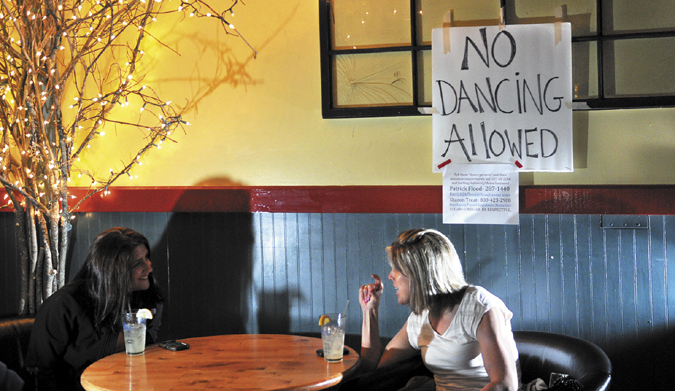 Ashley Gosline, right, chats with Hiedi LaLiberte while listening to the The Scolded Dogs band at Higher Grounds in Hallowell Friday. The Office of the State Fire Marshal recently cracked down on establishments that permit dancing that don't meet code. The Scolded Dogs normally play to a packed house with several people dancing.
