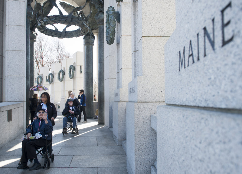 Veteran Dorothea Washburn, of Harrison, points to the Maine pillar Sunday as the Honor Flight New England tour arrives at the World War II Memorial in Washington. Washburn served as a Navy storekeeper 1st Class at the Brooklyn Navy Yard.
