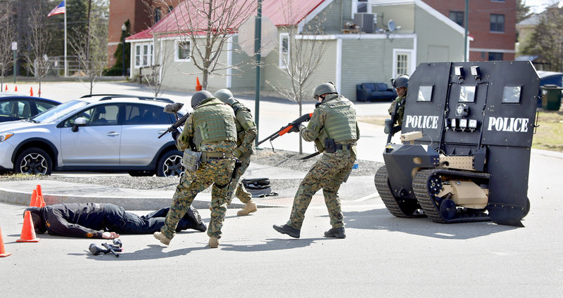 "Members of the Southern Maine Special Response Team approach a ""suspect"" after being shot with paint balls during a demonstration of the ""SWAT Bot"" at the Sanford Police Department on April 18, 2013. The ""Swat Bot"", built by Howe and Howe Technologies, is the world's first remote tactical approach vehicle."