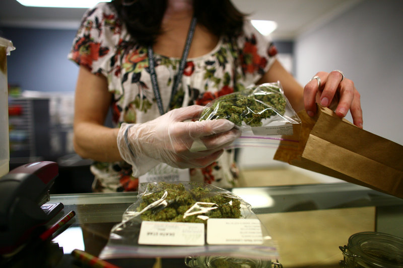 Sales associate Crystal Guess packages up a patient's order inside the Good Meds medical cannabis center in Lakewood, Colo. Washington and Colorado are the only two states that have fully legalized the drug.