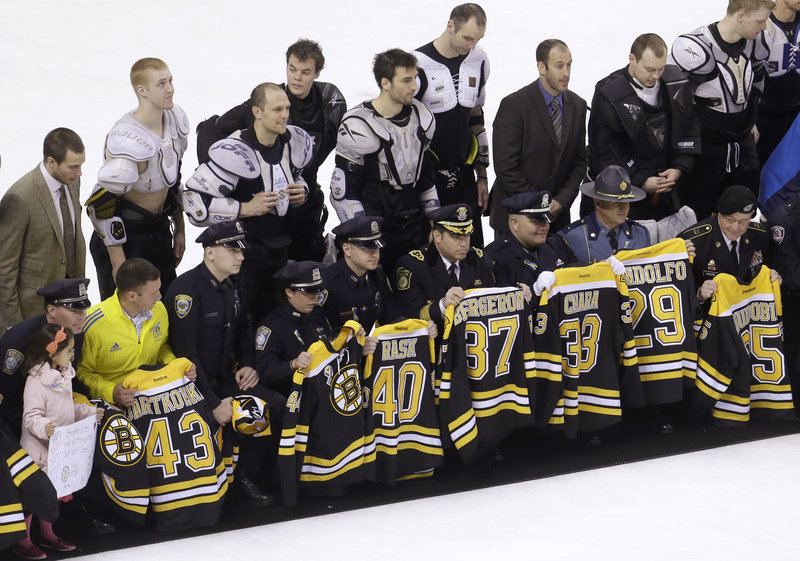 "First responders, members of law enforcement and Boston Marathon officials hold Boston Bruins jerseys they received in the Bruins' ""Shirt Off Our Backs"" ceremony."