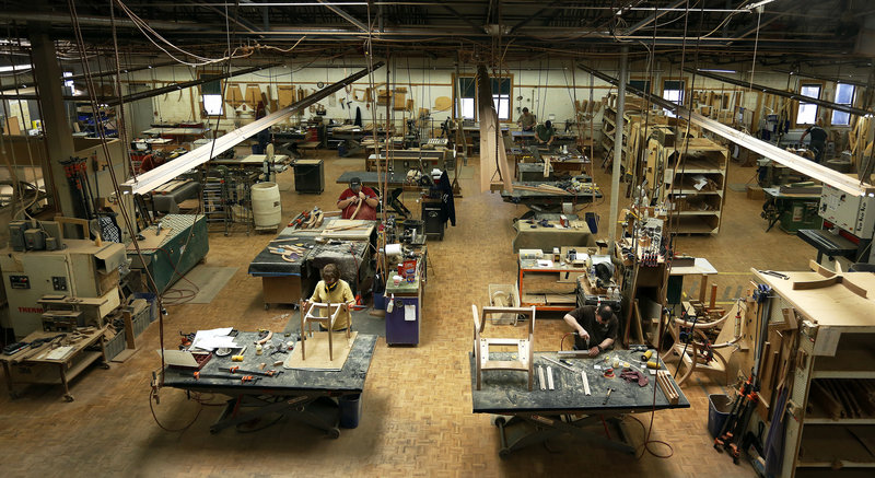 Cabinetmakers assemble chairs Thursday at the Thos. Moser facility in Auburn. Founded four decades ago by Bates College professor Thomas Moser, the company has built furniture for libraries and corporate boardrooms across the United States.
