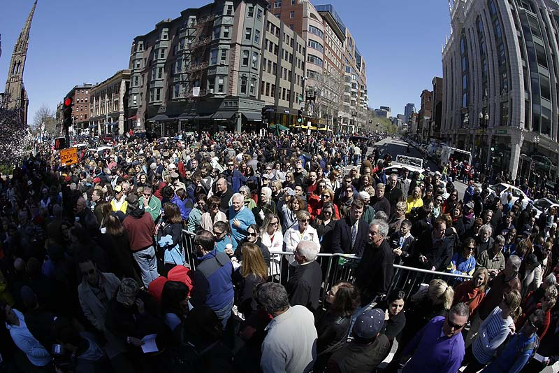 In this photograph made with a fisheye lens, people attend an interfaith service held near a makeshift memorial on Boylston Street, near the finish line of the Boston Marathon on Sunday.