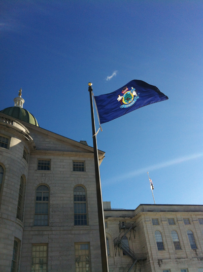 The Maine flag flies outside the State House in Augusta.