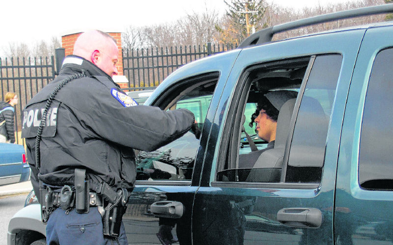 Patrolman Scott Perry from the Dunmore, Pa. Police Department distributes information cards on new seatbelt laws to students at Dunmore High School on Feb. 22, 2012. Augusta and Gardiner police will step up enforcement of seat belt laws over the next few weeks, as part of the national Click It Or Ticket campaign.