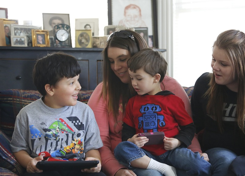Ja'kai Hayden, 8, left, spends time with his brother Javanni, 3, and cousins Courtney Courtemanche, 22, of Somersworth, NH and Brooke Spence, 11, right, of Dover, NH, on Saturday, March 9, 2013 during a family gathering in Portland.