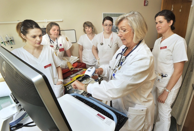 Betsy Moorhouse, a Central Maine Community College instructor, demonstrates log-on procedures for students using a mobile bedside medication verification computer in April.