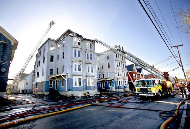 Firefighters work at the scene of a fire that destroyed two vacant apartment buildings on Bartlett Street in Lewiston on Monday morning. Fire Chief Paul LeClair said it took firefighters nearly four hours to bring the flames under control.