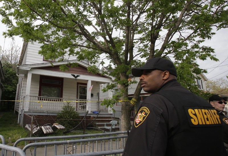 A sheriff's deputy stands outside a house from which three women escaped Tuesday in Cleveland.