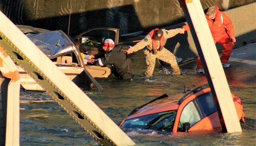 In this photo provided by Francisco Rodriguez, rescue workers form a human chain as they begin to remove a woman who reaches out from a smashed pickup truck that fell into the Skagit River after the collapse of the Interstate 5 bridge on Thursday in Mount Vernon, Wash.