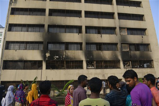 Workers stand outside an 11-story building that houses the Tung Hai Sweater Ltd. factory and apartments after a fire in Dhaka, Bangladesh on Thursday.
