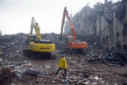 A rescue worker walks in the rain in the rubble of the garment factory that collapsed in Savar, Bangladesh.