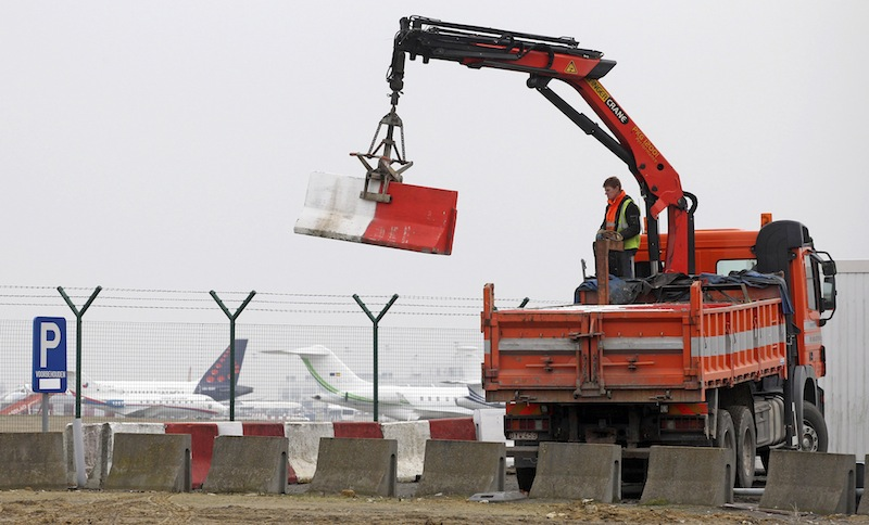 In this Feb. 19, 2013 file photo workers place concrete blocks to block access to a security fence next to the tarmac at Brussels international airport. Police carried out a series of raids on Wednesday, May 8, 2013, in Belgium and detained 31 people in three countries in connection with a spectacular $50 million diamond heist pulled off with apparent clockwork precision at Brussels Airport, a Belgian prosecutor said Wednesday. (AP Photo/Yves Logghe, file)