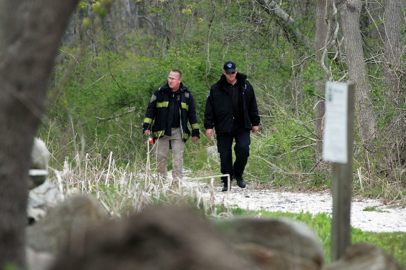 Massachusetts State Police walk out of the woods of The Smith Neck Farm in Dartmouth, Mass. on Friday, May 3, 2013 as federal, state and local authorities on Friday searched the woods near the UMass-Dartmouth campus as part of the marathon investigation. (AP Photo/The Standard-Times, John Sladewski)
