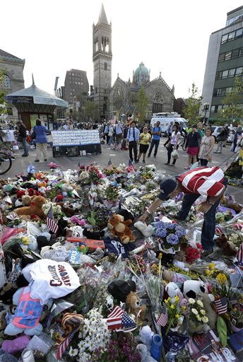 Volunteer Kevin Brown, of Boston, right, places a Teddy bear at a makeshift memorial near the Boston Marathon finish line in Boston's Copley Square on Tuesday in remembrance of the marathon bombing victims.