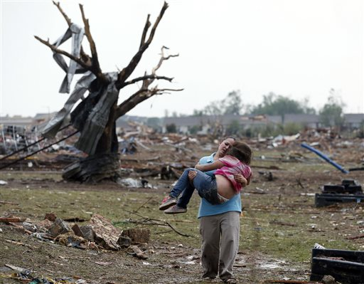 A woman carries a child through a field near the collapsed Plaza Towers Elementary School in Moore, Okla., on Monday after a tornado as much as a half-mile wide with winds up to 200 mph roared through the Oklahoma City suburbs.