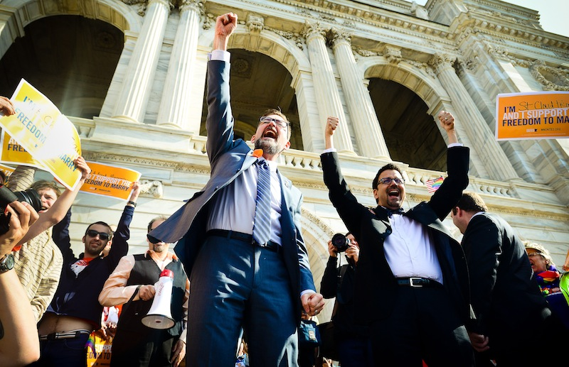 Sen. Scott Dibble, DFL-Minneapolis, left, sponsor of the gay marriage bill in the Minnesota Senate, and his partner Richard Leyva greet a large, joyous crowd as the arrive at the Minnesota State Capitol in St. Paul, Minn. on Monday, May 13, 2013. The Minnesota Senate is scheduled open debate at noon on a bill that would make Minnesota the 12th state to legalize gay marriage and the first to pass such a measure out of its Legislature. The chamber's majority Democratic leaders have said they expect it to pass and Democratic Gov. Mark Dayton has promised to sign it. (AP Photo/The St. Paul Pioneer Press, Ben Garvin) MINNEAPOLIS STAR TRIBUNE OUT