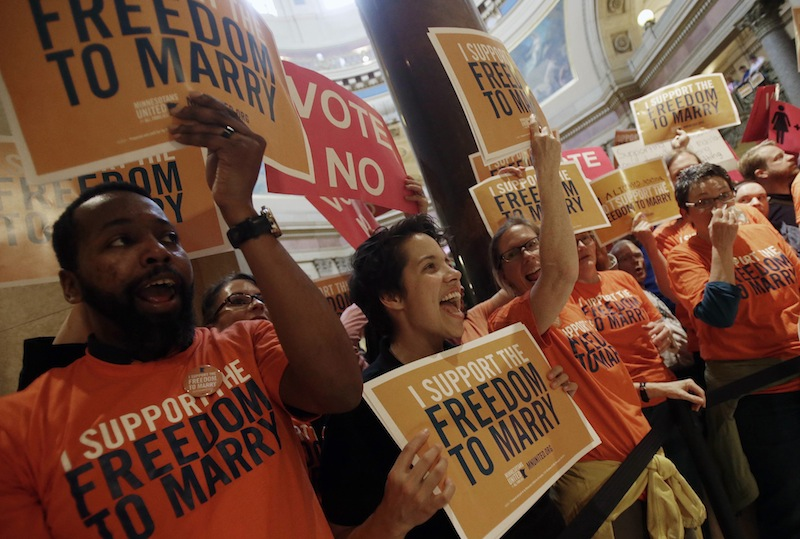 Demonstrators gather outside the Minnesota House chamber to greet lawmakers as they arrive to take up the gay marriage bill at the State Capitol, Thursday, May 9, 2013 in St. Paul, Minn. (AP Photo/Jim Mone)
