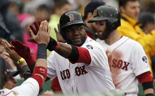 Boston's David Ortiz, center, and Dustin Pedroia, right, are greeted at the dugout after they both scored on a single by Daniel Nava during the eighth inning of their 7-4 win over the Cleveland Indians on Saturday at Fenway Park in Boston.