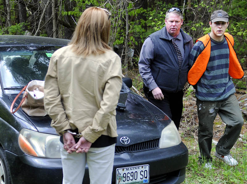 Kennebec County Sheriff's Office Detective Dave Bucknam, center, escorts Brock Hamilton, right, from behind a barn in Manchester Tuesday, which deputies claim he was burglarizing when they arrived. Deputies also detained Tonia Sirois, 30, of Augusta, left, who summonsed on theft and criminal trespass charges.