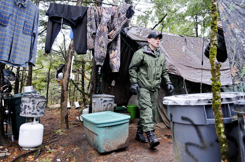 Staff photo by Andy Molloy District Game Warden Aaron Cross exits Christopher Knight's camp Tuesday April 9, 2013 in a remote, wooded section of Rome after police inspected the site where Knight is believed to have lived since the 1990s. Police believe Knight, who went into the woods near Belgrade in 1986, was a hermit who committed hundreds of burglaries to sustain himself.
