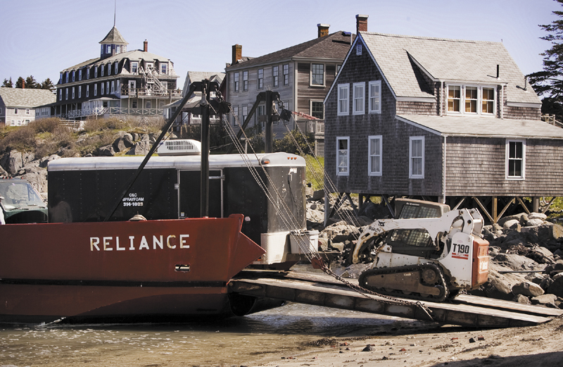 As part of an Island Institute program to make Maine island homes more energy efficient, contractors are transported via barge to Monhegan to eliminate air leaks on many island homes with weather sealing and spray insulation.