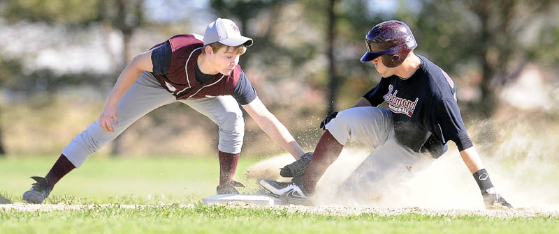 Richmond High School's Eddie Stewart slides safely under the tag by Buckfield High School's Owen Bennett at second base Tuesday in Richmond. The Bobcats won 5-4. For local roundup, see C3.