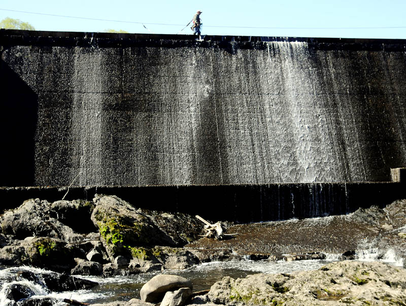 Jeremy Gorman walks on the lip of the American Tissue Dam Tuesday on Cobbossee Stream in Gardiner while deploying safety barrels. Wearing a safety harness and hooked onto a cable, Gorman said the barrels were deployed in the current to deter boaters from approaching the 20 foot drop off at the hydro-electric dam.