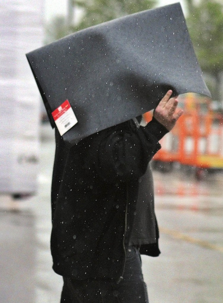 James Dunlop, of Richmond, holds a floor mat he purchased over his head Wednesday while exiting Home Depot in Augusta in pouring rain. The clouds are expected to dissolve by Thursday and temperatures may climb in to the 90s by Friday, according to forecasts. Dunlop said the mat will be placed in front of the sink at his home.