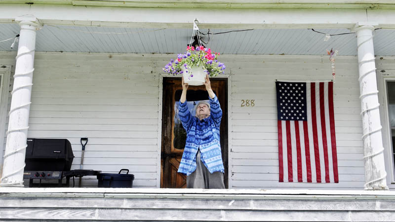 Ann Gleason hangs a flower basket Tuesday on the porch of her Manchester home. Blue skies prevailed as Gleason watered her plants. The weather is forecast to remain mild with clear skies through the remainder of the week.