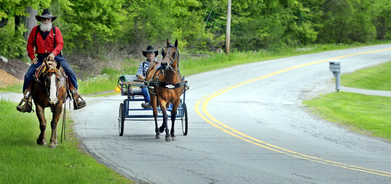 """Dan Boyd, left, and his son, Gary, ride through Vassalboro Thursday with a pair of steeds during their nationwide tour of the United States on horseback. The riders have crossed several southern states since their journey commenced in September of 2012 and hope to cover the eastern seaboard this year. """"The Lord put it in my heart,"""" Dan Boyd, a pastor from Kansas, said. """"We plan to preach on the way."""""""