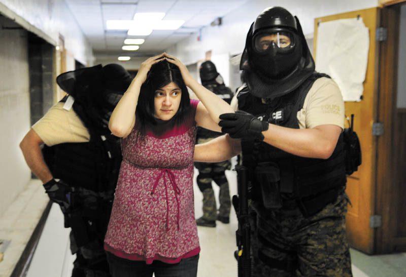 Kaitlynn Littlefield is escorted Wednesday from the former Hodgkins Middle School in Augusta by a member of Augusta Police Department's special response team during hostage negotiation training in Augusta. Littefield and four colleagues from Crisis in Counseling portrayed hostages while law enforcement students from Thomas College and the University of Maine at Augusta depicted armed gunmen barricaded in a classroom, according to Augusta Police Lt. Kevin Lully. Negotiators from the Lewiston and Augusta Police Departments practiced persuading the hostage takers to surrender during the day-long training.
