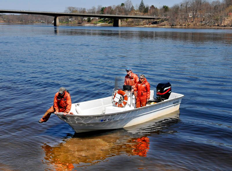 Maine Department of Marine Resources technician Jason Beaudry leaps out of a boat in Gardiner recently after searching the Kennebec River with biologists Jason Bartlett, center, and Gail Whipplehauser with a side scan sonar between Gardiner and Augusta. According to Whipplehauser, the scientists are collecting data on the migration of sturgeon, shad and herring that spawn in the river through mid-July.