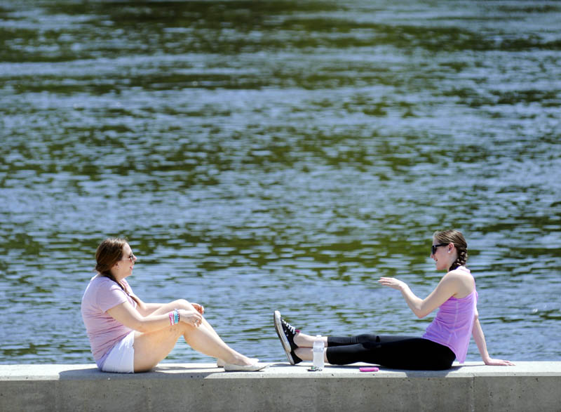 Simera LeBlanc, left, and Katie Formanski, of Litchfield, share some sun Thursday on the bulkhead along the Kennebec River near LeBlanc's home in Hallowell. The temperature reached into the mid 80s.