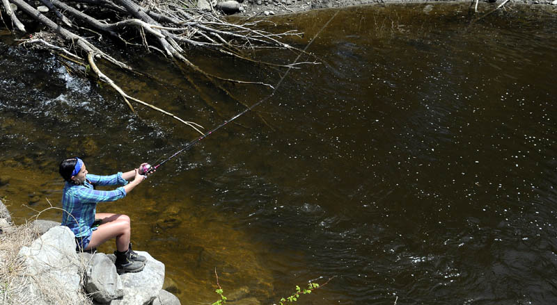 Kaysie Dostie casts into Bond Brook on Monday while fishing on her grandfather's land in Augusta. Dostie said she lost a fish but expected a few more to strike her worm.