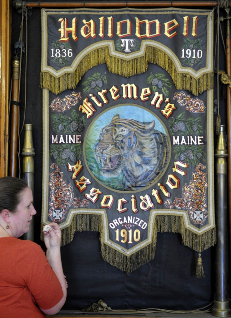 """Camille Myers Breeze inspects a smudge sample from the painted silk banner hanging at the Hallowell Fire Department on Wednesday. Breeze, of Museum Textile Services of Andover, MA, assessed the condition of the banner that is believed to date from 1910 to determine its condition and work warranted to restore it. The banner was carried during processions at musters by the Hallowell Firemen's Association """"It's one of the nicest painted silk banners I've ever seen,"""" Myers Breeze said. The tiger depicted in the banner was the name of the department's engine at the turn of the 20th century."""