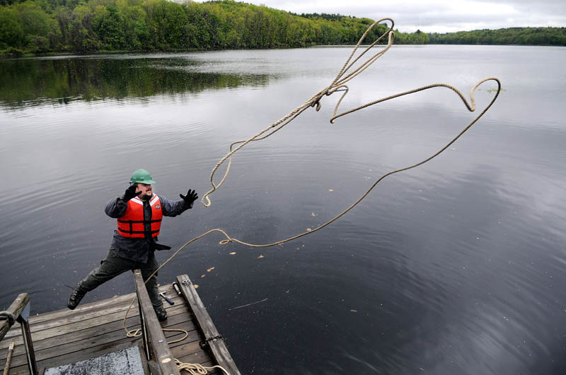 Maine Bureau of Parks and Lands employee Matt Myshrall tosses a line to shore from a dock he helped install Monday on the Kennebec River in Hallowell. The state is laying out the docks along the river for summer.
