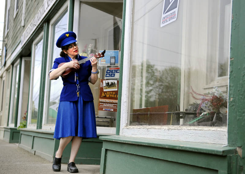 "Justine Fontes strums a ukulele on Thursday outside the Readfield Post Office, where she is serving as the relief postmaster. The stringed music serenades customers collecting mail and people walking down the main street of Readfield, according to Fontes. ""04355 is the best little zip in Maine,"" Fontes said."