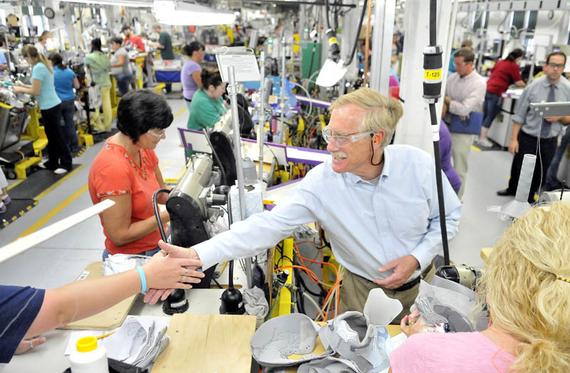 Angus King, center right, shakes hands with a New Balance employee during a campaign tour of the Skowhegan factory on Aug. 14.