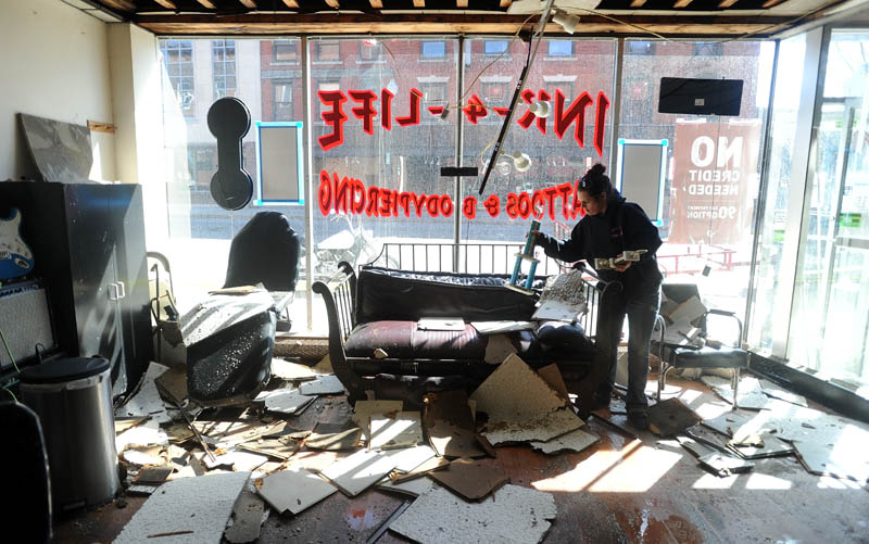 Mona Juliano sifts through salvage from her tattoo studio, Ink-4-Life, in downtown Waterville Saturday morning.