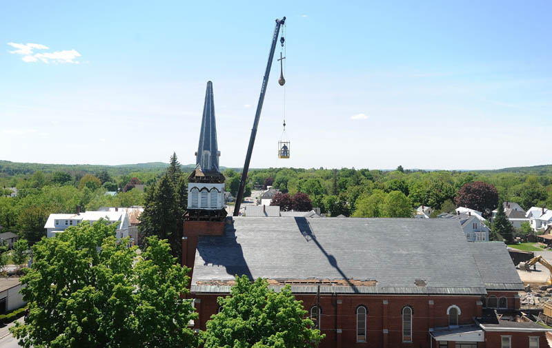 The cross that stood atop the steeple of Saint Francis de Sales Catholic Church in Waterville is hoisted over the church as the steeple is removed by sections during demolition on Tuesday.