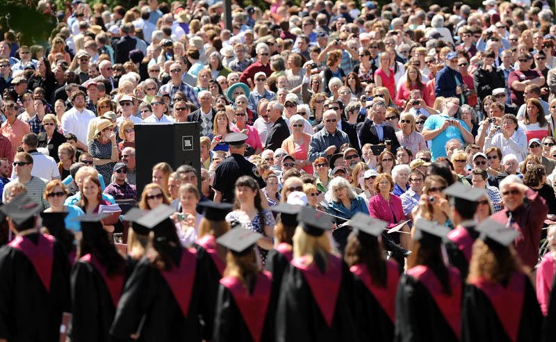 Graduates of the University of Maine at Farmington march past friends and family on High Street during commencement ceremonies in Farmington on Saturday.