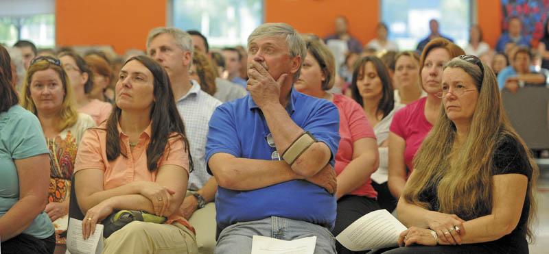 Wayne Cormier, center, listens to a PowerPoint presentation at Messalonskee Middle School during a special school board meeting Thursday night.