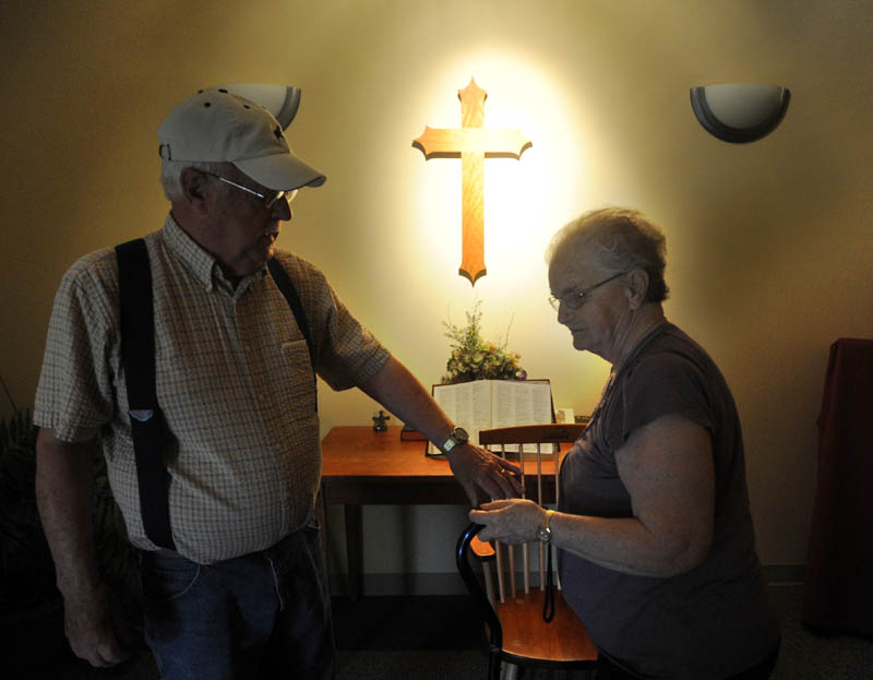 "Gerald ""Jake"" Ellis, 79, reaches for the hand of his wife Pauline Ellis, 79, after saying the Lord's prayer in the chapel at Lakewood Nursing Home in Waterville Wednesday morning. Pauline is a resident in the nursing home's dementia ward."
