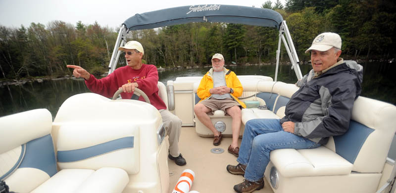 Mel Croft, left, leaves his dock on East Pond with Rob Jones, center, and Gordon Woods, right, to install speed-limit buoys Friday morning at both ends of the Serpentine, a mile-long, narrow stretch of shallow water that connects East Pond with North Pond. Croft is also a volunteer for LakeSmart, an environmental program.
