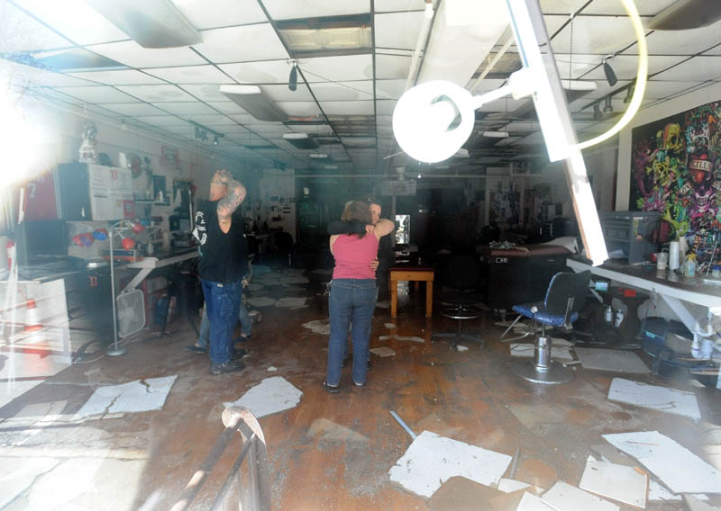 Mona Juliano, center facing, co-owner of Ink-4-Life, receives a hug from a tenant in a Main Street building in downtown Waterville, which was destroyed by a fire Friday afternoon, as they clean up their shop Saturday morning.