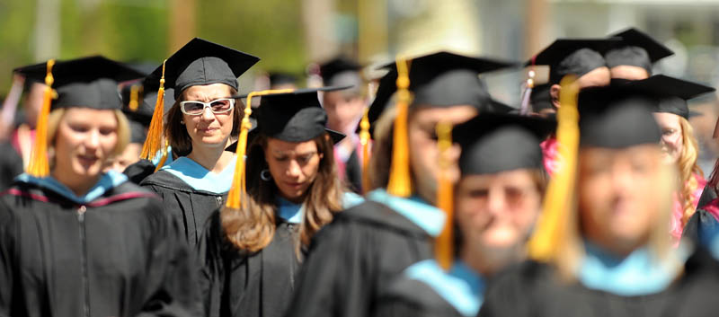 Graduates of the University of Maine at Farmington march down High Street during commencement ceremonies in Farmington on Saturday.
